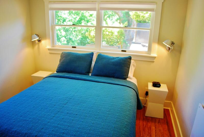 Cozy bedroom with tree filled windows & queen size bed plus ample storage