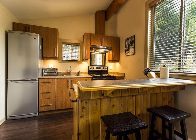 Port O' Pierre cottage's kitchen with full fridge and stove.