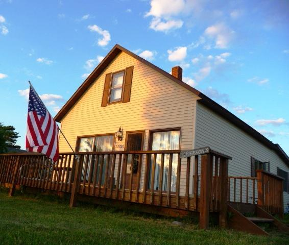 The front of the cottage, with a deck and a beautiful view of the sunset on the harbor