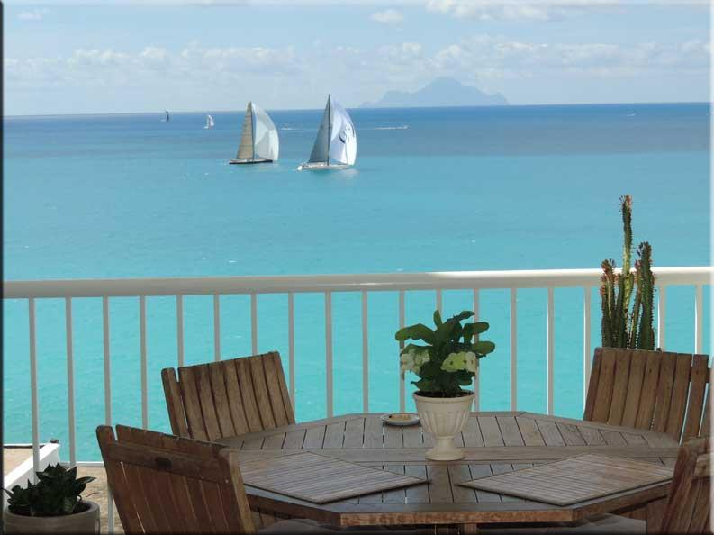 Dining table on Caribbean balcony with sailboats and Saba