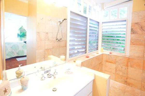 Spacious master bath has a large pink marbele shower, separate toilet room opens out to living room