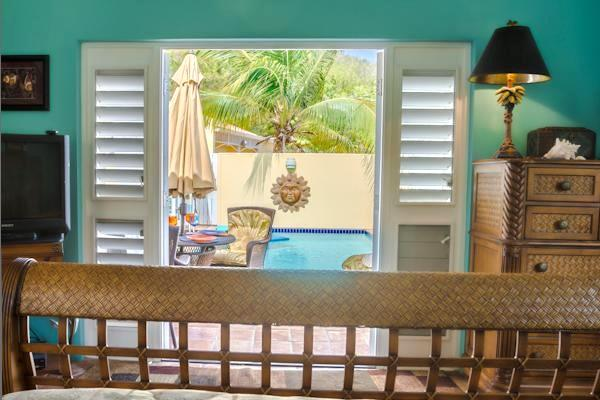 Guest bedroom looks out two french doors to the pool