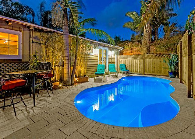 Brand new private pool with lounge seating, bistro table, and tropically landscaped surroundings