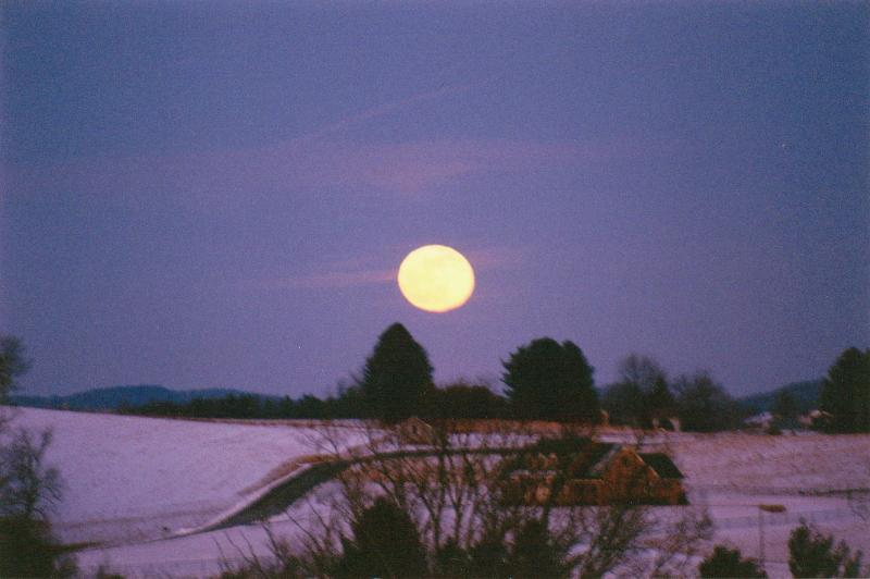 Full moon rising over snow behind cabooses