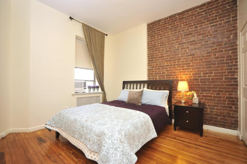 Master bedroom with queen size bed with 100% cotton bed linens- original exposed brick wall accent