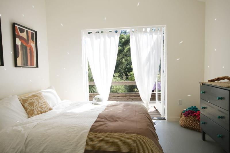 Master bedroom. Queen bed. Private deck overlooking the pool. No alarm needed, leave it to the birds