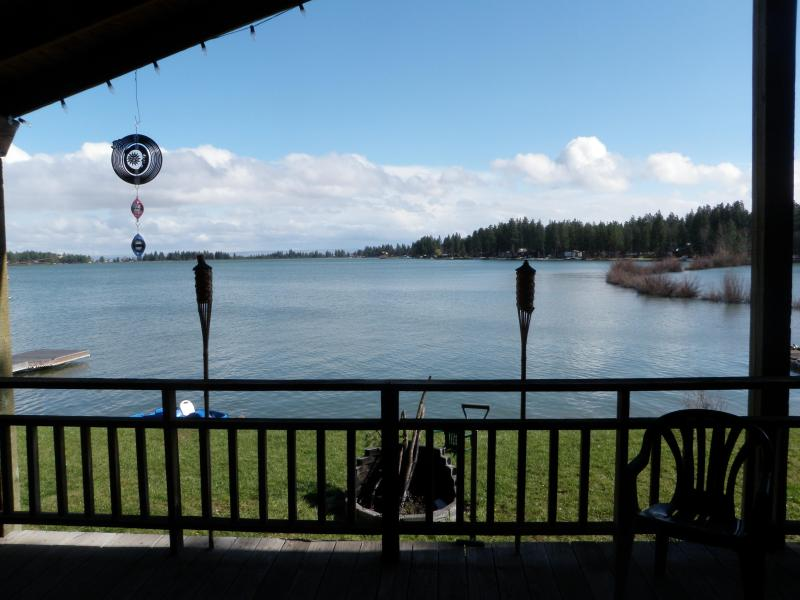 view of lake from the wall of windows in the great room and the covered patio
