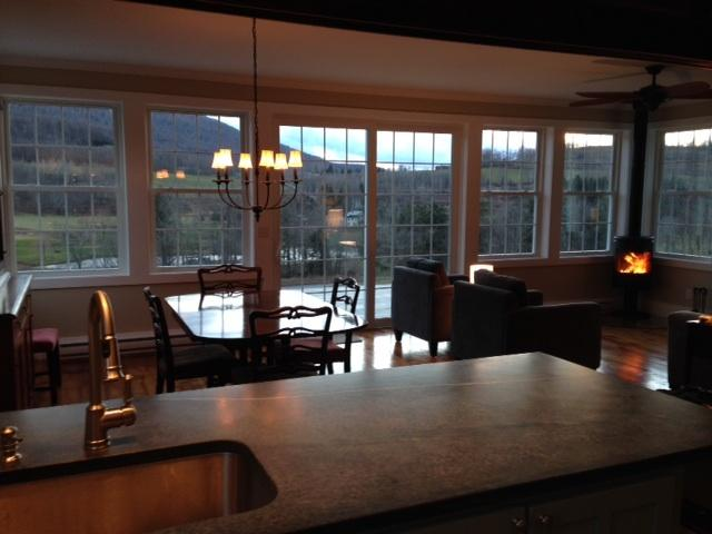 View from kitchen of open floor plan with wall-to-wall windows facing mountain views.