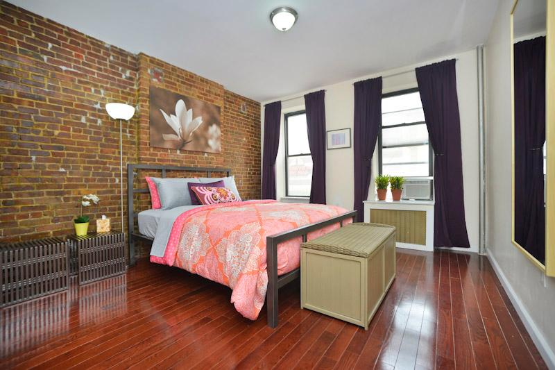 Master Bedroom 1- Queen bed, original exposed brick wall, hardwood flooring throughout apartment