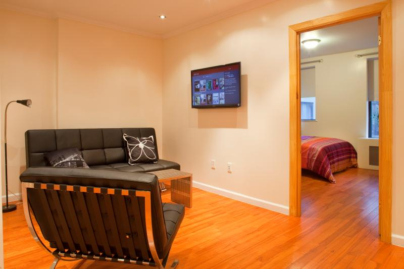 Living area with flat screen TV, hardwoor floors throughout apartment