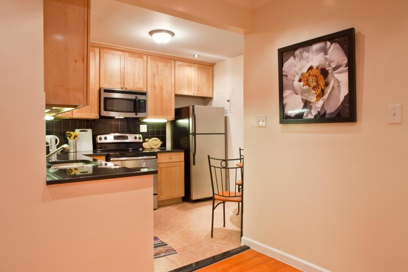 Eat in kitchen with stainless steel appliances and black granite countertop