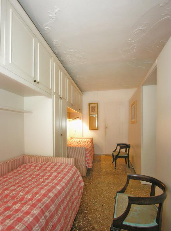 The bedroom with 2 single beds behind the library