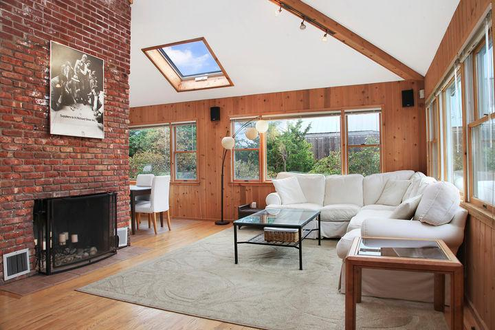 Open Light airy living room..high ceilings, working fireplace, skylights, tons of light!