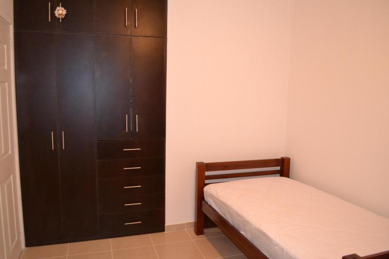Segunda habitación con dos camas y un armario.