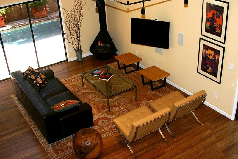 Living room with barcelona chairs, tv with surround sound, gas fireplace, overlooking poo.
