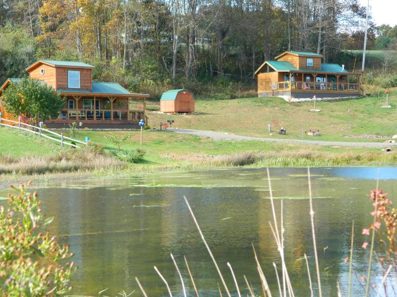 Two cabins overlooking a stocked mountain pond.