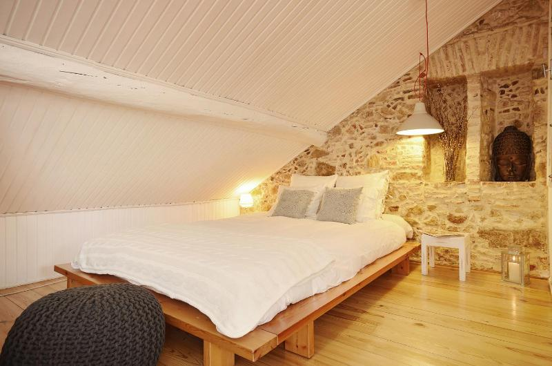 The large double bed sits against an original, stone wall adding a rustic and traditional feel