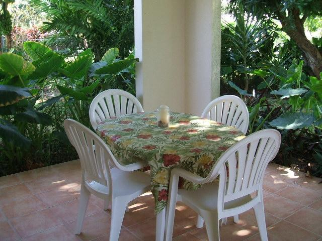 Covered patio dining area surrounded by lush gardens.