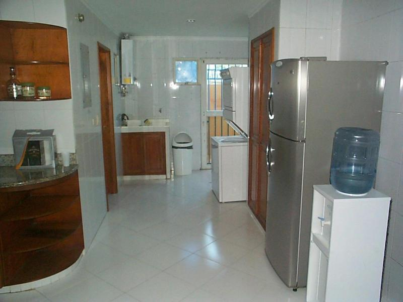 Laundry area of kitchen with adjacent maids quarters with bathroom.