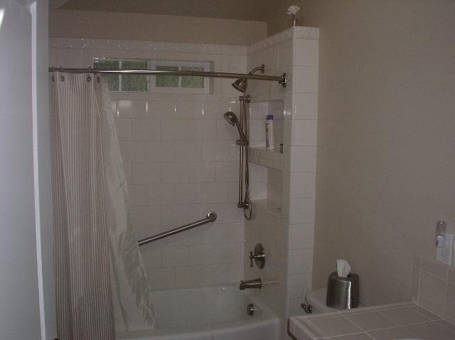 Azulejo de ducha con ducha doble y barras de agarre