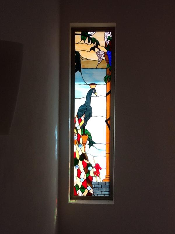 Stained glass window in stairwell leading to master bedroom