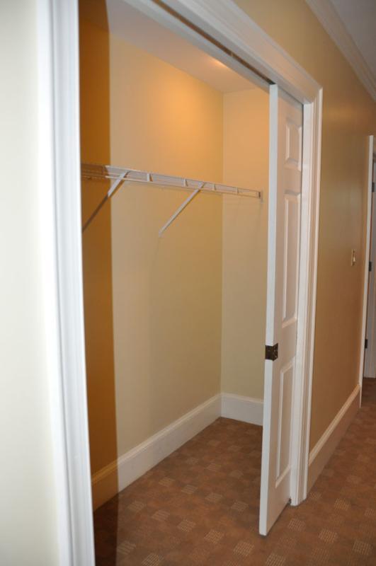 Hallway closet for jacket and suitcase storage.