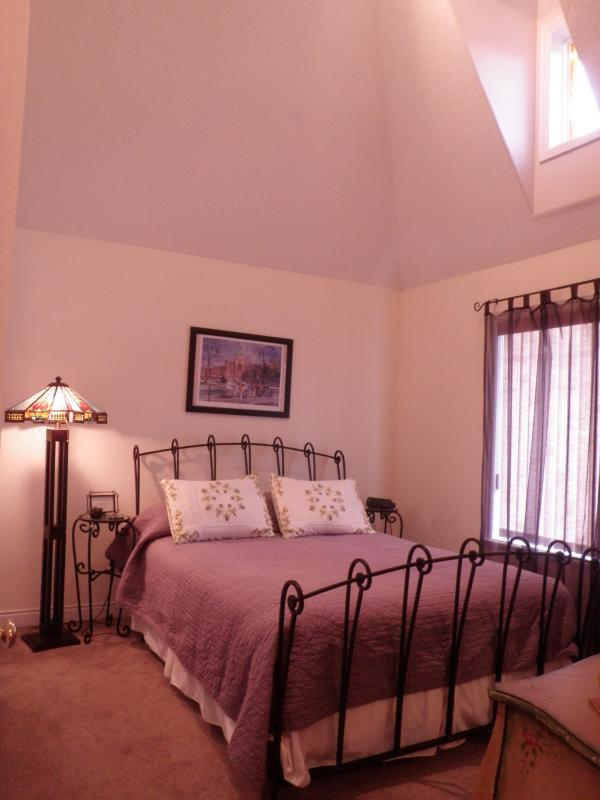 Second bed room with Queen sized bed, cathedral ceiling  andstained glass window.