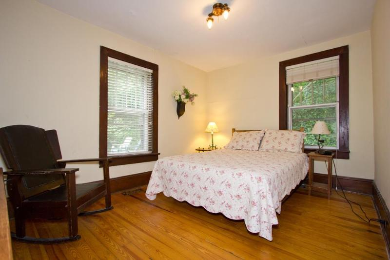 Master bedroom features queen size bed, quilted bedding, Arts & Crafts style furniture.