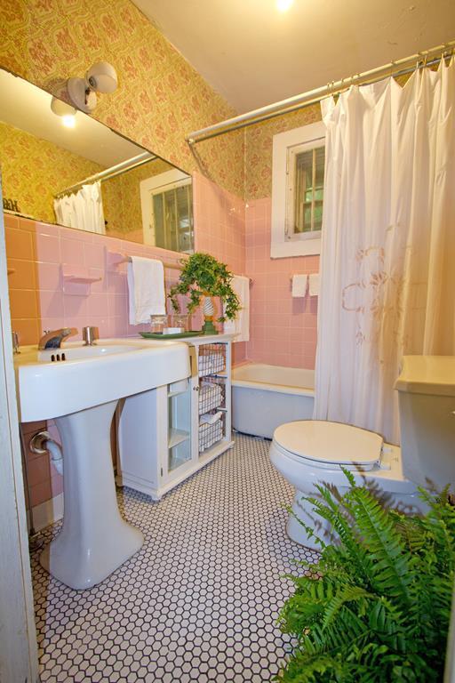Vintage bathroom, original soaking tub with shower option, original sink, black & white tile