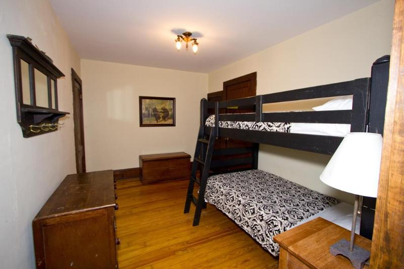 Dancing Bear bedroom.  Bunk beds, blanket chest, desk and chair, luggage rack.