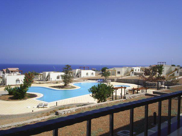 Balcony view with panoramic sea views and large swimming pool