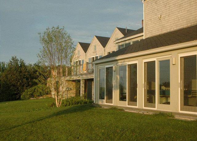 Extérieur arrière de la maison, avec de nombreuses fenêtres et portes coulissantes.