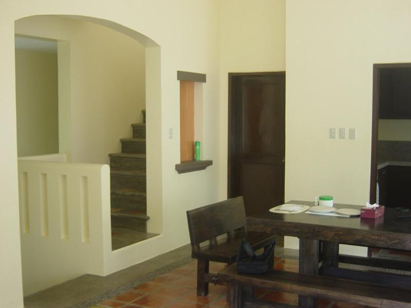 Guest bedroom door at center. Kitchen door to right. Dining table partially visible sits 14.