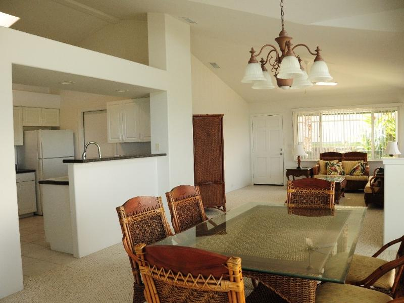 Living and dining area next to kitchen with microwave and dishwasher.