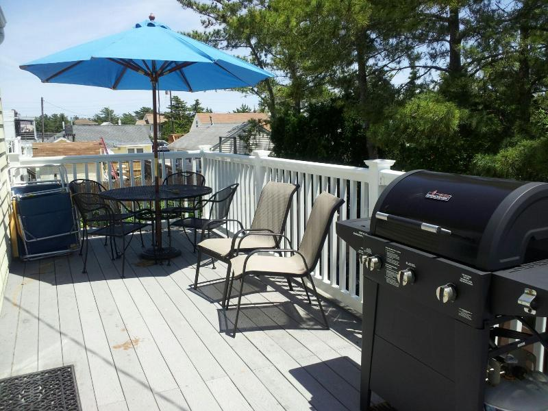 OUTSIDE OCEANSIDE DECK WITH TABLE & CHAIRS & DECK UMBRELLA & GAS GRILL