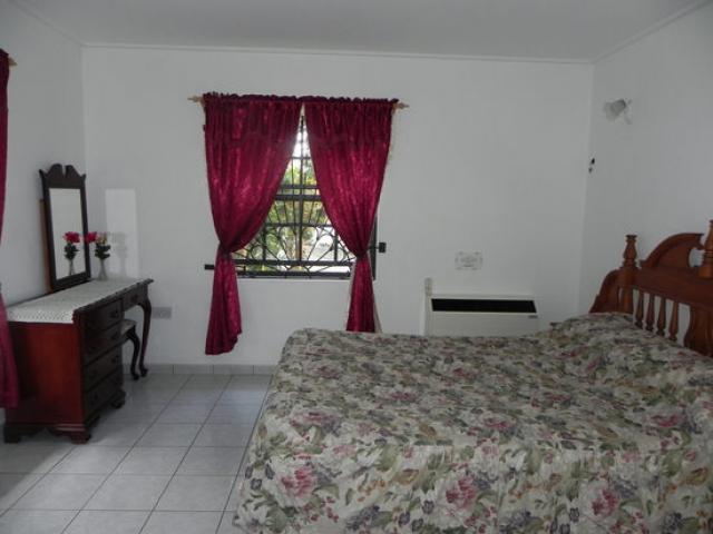 ruime slaapkamer met queen size bed en airconditioning