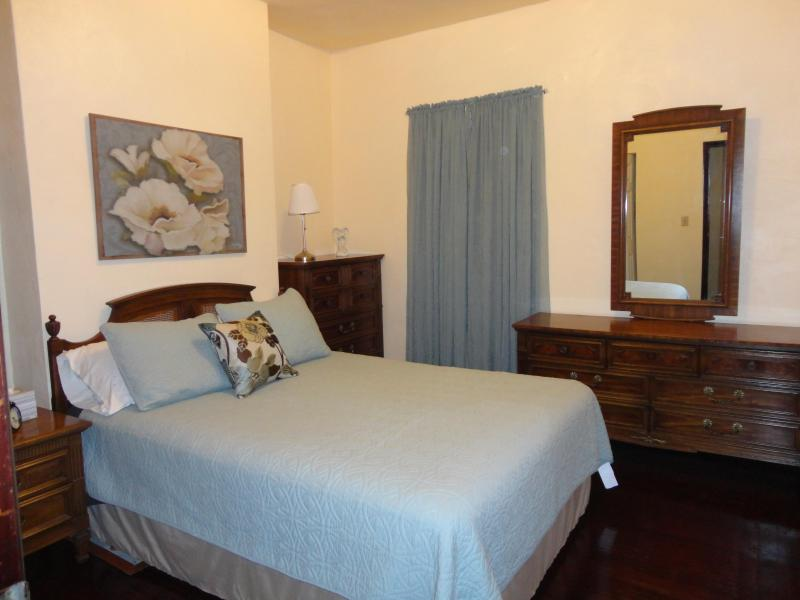 Bedroom 1 features soothing shades of blue, a comfortable Queen bed, & vintage solid wood furniture.