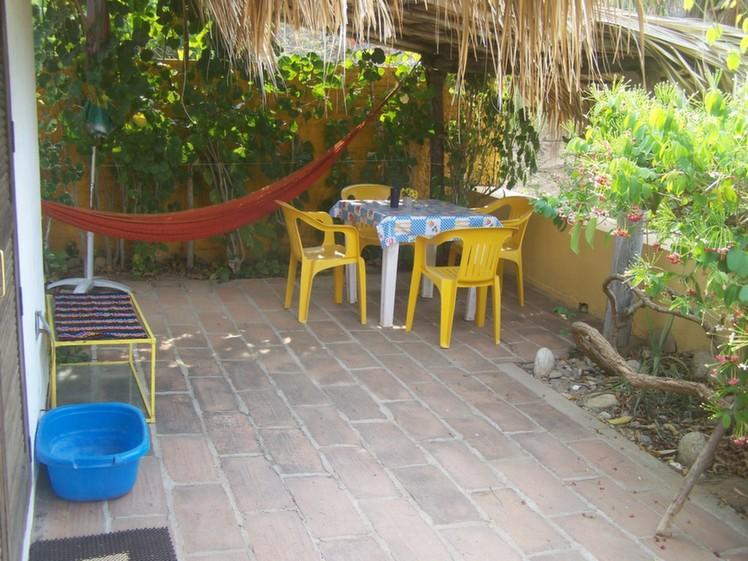 Palapita terrace with table, chairs, hammock and blue footbath.