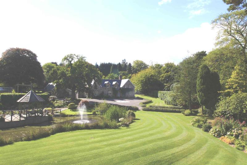 Widcombe Grange across the sweeping lawn, beside the lake