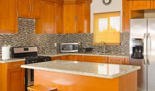 Cocina con castaña de madera teñida gabinetes y salpicadero mosaico
