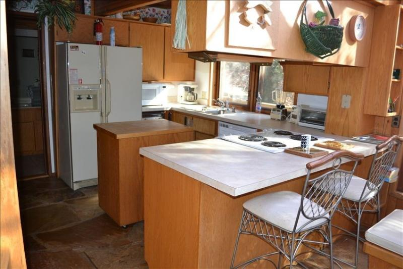 Enjoy nature while cooking in fully equipped kitchen with butcher block island & separate bar area!