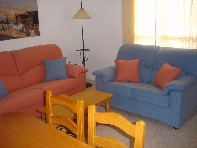 Séjour avec deux canapés, 2 tables, 6 chaises et un bar.