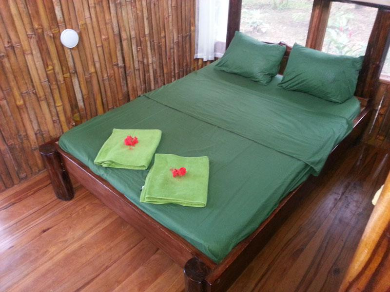 Bedroom one with queen bed and jungle view, leads to shower and toilet.