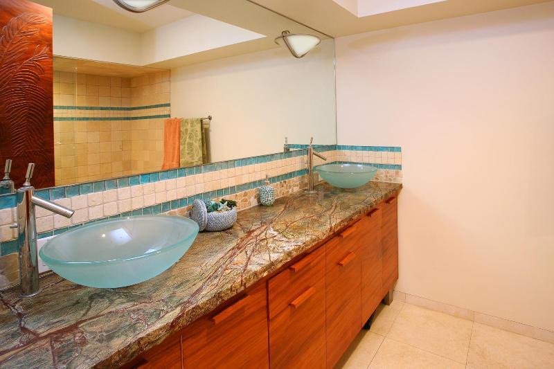 Bathroom w/ rainforest granite counters, custom zen koa cabinetry, glass vessels