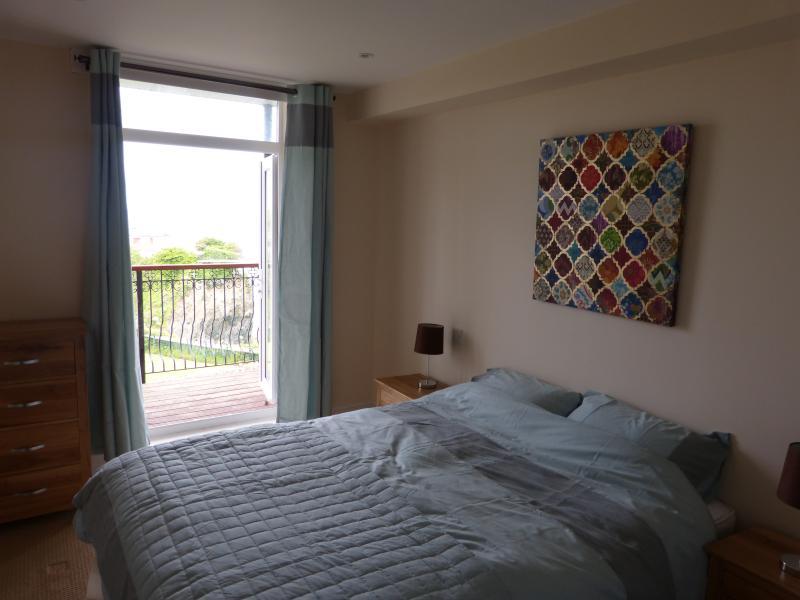Dormitorio principal - acceso a balcón y vistas a la playa de Towan y la isla