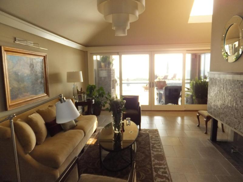 living room with pool and ocean beyond. Fireplace at right. Another fireplace in the oceanview patio