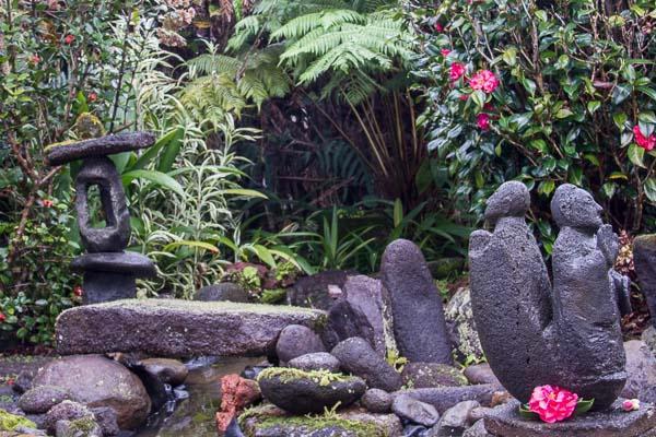 Las esculturas de piedra disfrutan la paz y la beauity en los jardines de nuestra casa de Aloha.