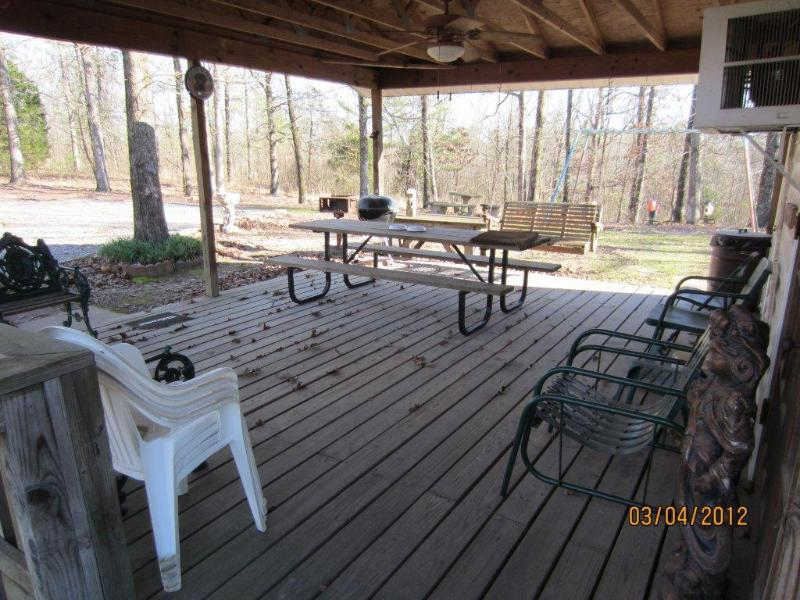 Deck under roof with picnic table, swing, grill