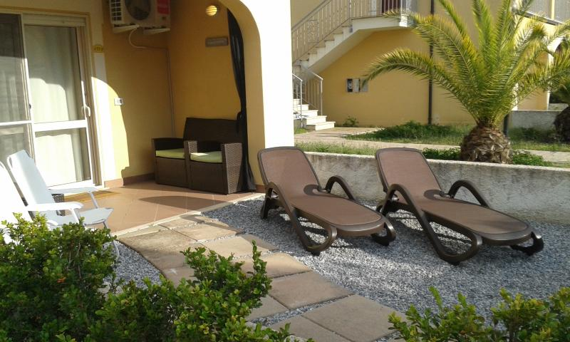 Garden with mosquito screens, sun loungers, dining suite and deck chairs