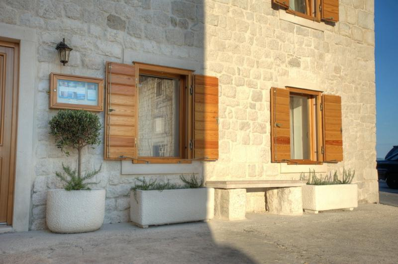 Front of building with hand carved stone seating and olive bushes